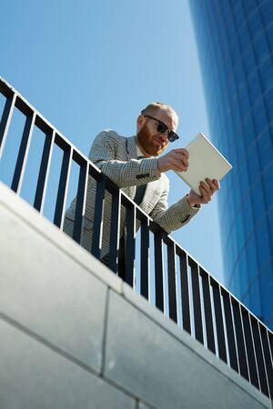 Bearded businessman examining data on tablet Stock Photo