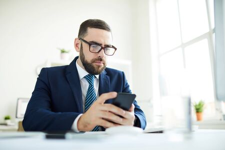 Business manager checking phone in office
