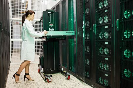 Attractive woman working in storage room of mining farm Stock Photo