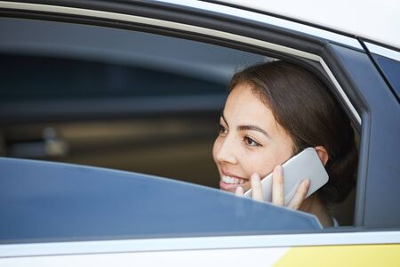 Smiling Woman Speaking by Phone in Car