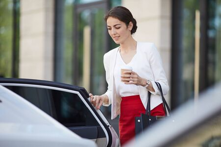 Businesswoman Getting into Car