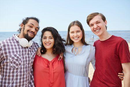 Vier vrienden poseren aan zee