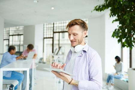 Content guy chatting online in co-working space Stock Photo