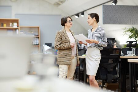 Side view portrait of two contemporary businesswomen discussing work plans while standing in office, copy space Stock Photo