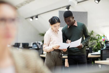 Portrait of two business interns discussing documents standing in modern office, copy space