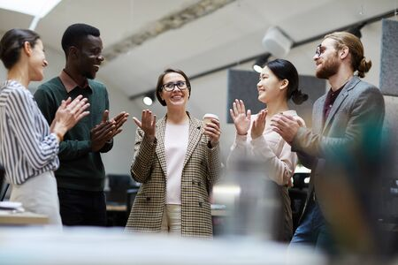 Waist up portrait of multi-ethnic group of business people applauding cheerfully while celebrating promotion during coffee break in office, copy space
