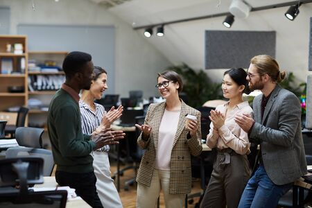 High angle view at multi-ethnic group of business people smiling cheerfully while chatting during coffee break in office, copy space Stock Photo