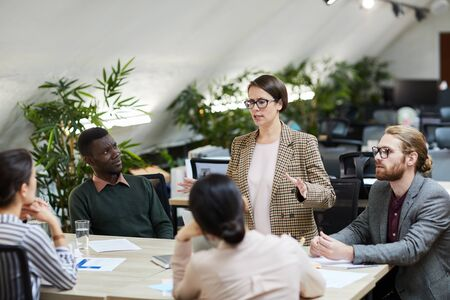 Portrait of successful female manager giving presentation during meeting with colleagues, copy space Stock Photo