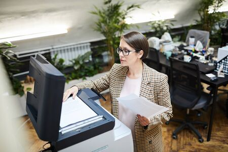 High angle portrait of young businesswoman scanning documents while working in office, copy space