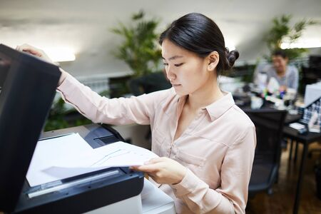 Portrait of Asian businesswoman scanning documents while working in office, copy space Stok Fotoğraf