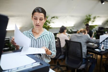 Waist up portrait of young businesswoman scanning documents while working in office, copy space