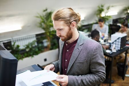 High angle portrait of handsome businessman printing documents while working in office, copy space