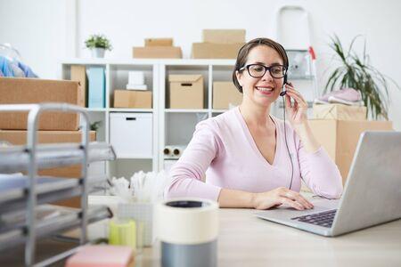 Souriant jeune opérateur de service d'assistance dans un casque parlant dans un microphone tout en étant assis devant un ordinateur portable par bureau Banque d'images