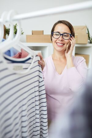 Young cheerful woman looking through new casualwear seasonal collection while talking on the phone Stockfoto