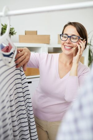 Happy casual female with smartphone looking through new seasonal collection in boutique or mall