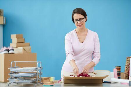Bella donna in pullover che annoda il nodo sopra il pacco per il cliente del negozio online mentre lavora in ufficio