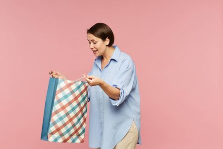 Young excited female in casualwear looking at surprise in open paperbag while posing in isolation