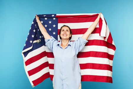 Happy young casual woman raising hand while holding large American flag on blue background 版權商用圖片