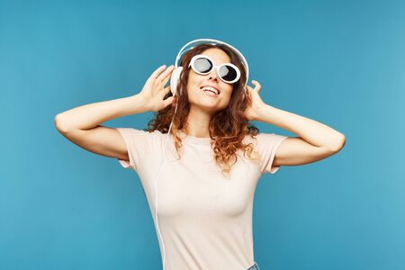 Happy young carefree female in headphones enjoying music at break in isolation over blue background