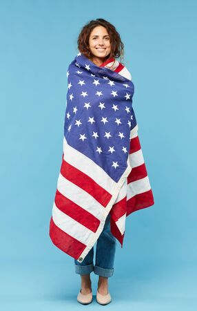 Happy young brunette female wrapped into American flag looking at you while standing in front of camera in isolation