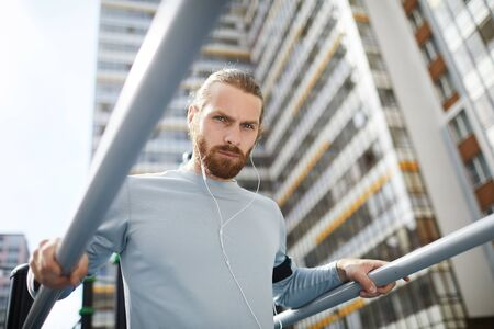 Portrait of handsome young bearded man in wired earphones standing on public sports ground and training on parallel bars
