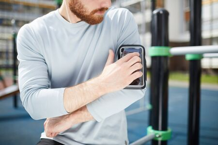 Close-up of serious red-bearded man in sweater standing on sports ground and fixing smartphone in case on shoulder Banco de Imagens