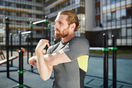 Serious pensive young man with red beard standing on modern equipped sports ground and stretching bicep of arm 版權商用圖片