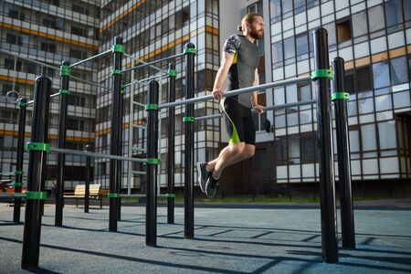 Tireless muscular athlete with red beard hanging on parallel bars while practicing pull-ups on training ground