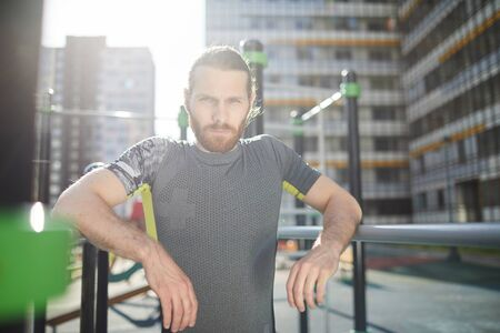 Portrait of serious determined handsome workout athlete with red beard leaning on parallel bars on outdoor ground