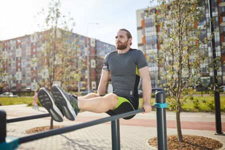 Serious young athlete with red beard keeping own body on straight arms while hanging on parallel bars outdoors