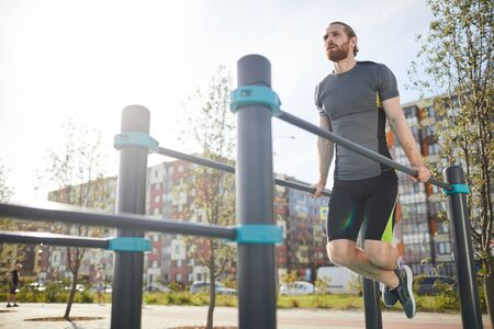 Red-bearded man in sportswear hanging on parallel bars and looking into distance while training on backyard of apartment building