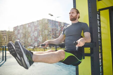 Concentrated young bearded man in sportswear hanging on parallel bars and exercising on bars outdoors