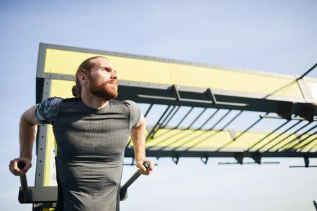 Serious pensive free young bearded man in tight tshirt doing pull-ups on bar while practicing strength exercise Banco de Imagens