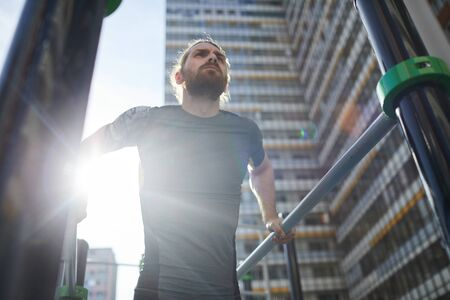 Below view of determined bearded athlete in tshirt hanging on parallel bars and looking into distance on outdoor ground