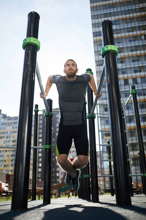 Determined young bearded man in sportswear using outdoor pull-up bars for training near house