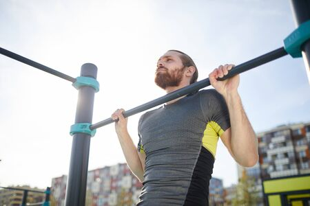 Concentrated determined young bearded guy in tshirt hanging on outdoor bar and lifting own body up