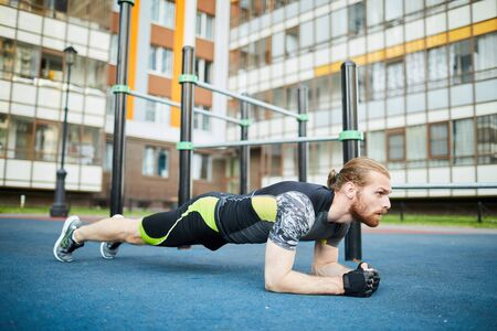 Serious motivated young man with beard and ponytail leaning on elbows while doing plank outdoors