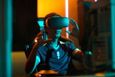 Jugador masculino joven positivo en camiseta sentado en la mesa y usando el simulador de realidad virtual mientras juega un videojuego