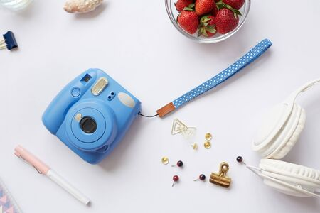 Above view of white background with instant camera, headphones, clips and pins, copy space Imagens