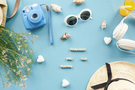 High angle view of small cubes with letters, instant camera, grass, shells, sunglasses and hat on blue background, vacation at sea concept