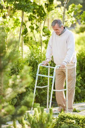 Full length portrait of senior man leaning on walker outdoors in sunlit park, copy space Stock Photo