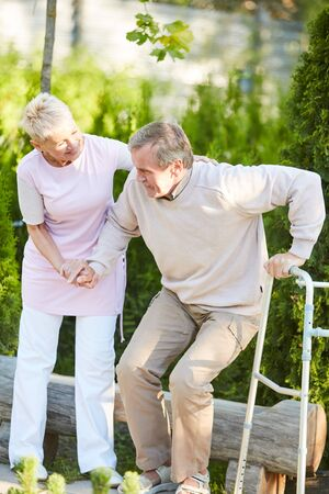 Full length portrait of caring nurse helping senior man get up from park bench in rehabilitation center, copy space