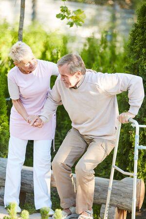Ritratto a figura intera di un'infermiera premurosa che aiuta un uomo anziano ad alzarsi dalla panchina del parco nel centro di riabilitazione, copia spazio