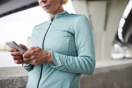 Mature sportswoman in windbreaker texting or scrolling in smartphone while having break after jog training in urban environment