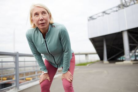 Tired mature sportswoman leaning on bent knees while standing on city bridge after jogging workout in urban environment