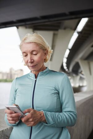 Contemporary active blonde mature female in sportswear scrolling in smartphone in urban environment Reklamní fotografie - 127586344