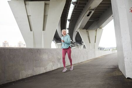 Mature active sprinter in sportswear and headphones jogging along modern bridge by riverside in urban environment