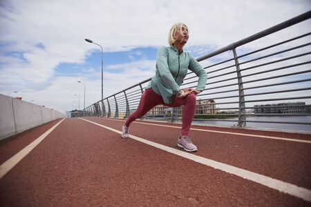 Active blonde mature female in sportswear doing exercfise for stretching on racetrack at stadium in urban environment Stock Photo