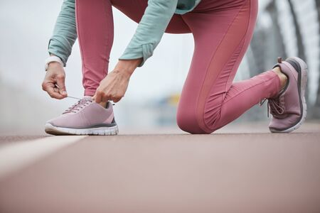 Low section of mature contemporary sportswoman tying shoelace of one of sneakers on racetrack at stadium Stok Fotoğraf