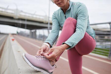 Reife zeitgenössische Frau in Activewear, die Schnürsenkel von Turnschuhen bindet, während sie auf der Rennstrecke in der städtischen Umgebung steht